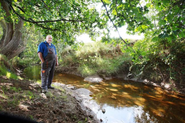 Geoff Hutchingson picture with the beck on his farm land near Greatham where he has already lost five of his calves due to low water levels after work was done further up stream to remove a weir Picture: SARAH CALDECOTT